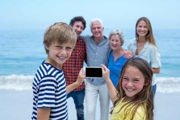 Happy siblings photographing family with smartphone