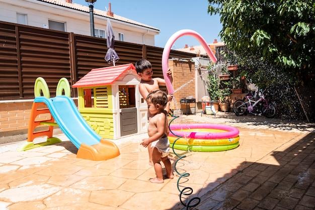 행복한 형제 자매는 뒷마당에서 물 호스를 가지고 놀습니다.
