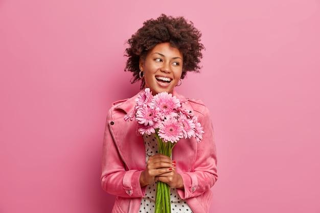 행복 한 성실한 아프리카 계 미국인 여자는 gerberas 꽃의 꽃다발을 들고 긍정적 인 축제 분위기를 가지고,