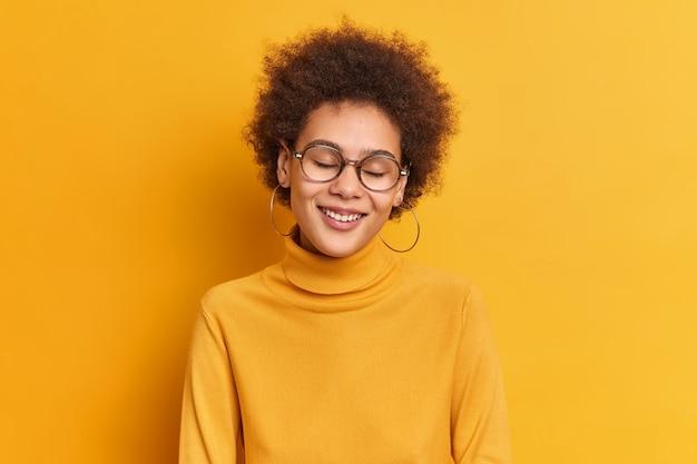곱슬 머리를 가진 행복한 성실한 밀레 니얼 소녀는 눈을 감고 부드럽게 미소 짓고 칭찬을받으며 캐주얼 한 폴로 넥을 입습니다.