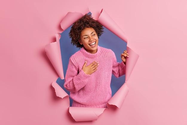 La giovane donna afroamericana felice e sincera ridacchia positivamente si sente molto felice di tenere la mano sul petto