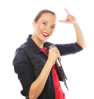 Счастливая поющая девушка. красота женщины в красной футболке с микрофоном на белом фоне.