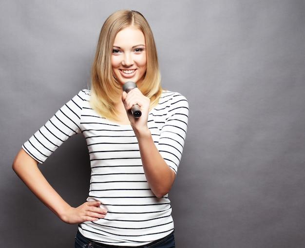Счастливая поющая девушка. красота женщины в футболке с микрофоном на сером