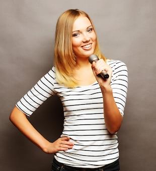 Счастливая поющая девушка. красота женщины в футболке с микрофоном над серым пространством.