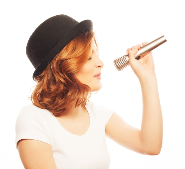 Счастливая поющая девушка. красота женщины в белой футболке и черной шляпе с микрофоном на белом фоне. хипстерский стиль.