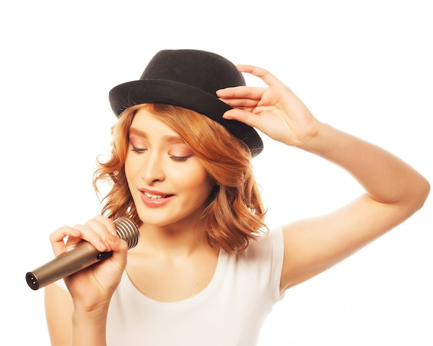 Happy singing girl. beauty woman wearing white t-shirt and black hat with microphone over white . hipster style.
