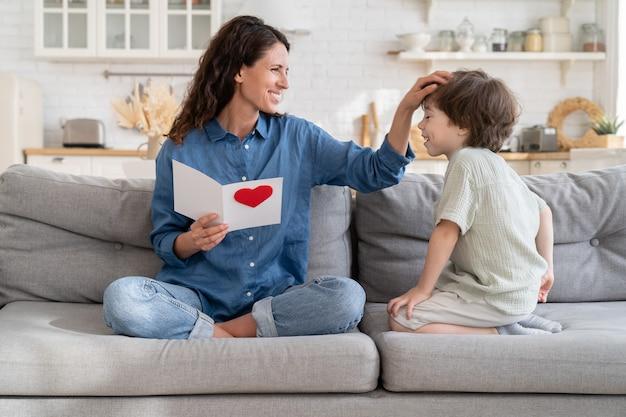 幸せなシングルマザーは、小さな息子と一緒にソファに座ってグリーティングカードを保持するギフトママのためにタンク一杯の子供の髪に触れます