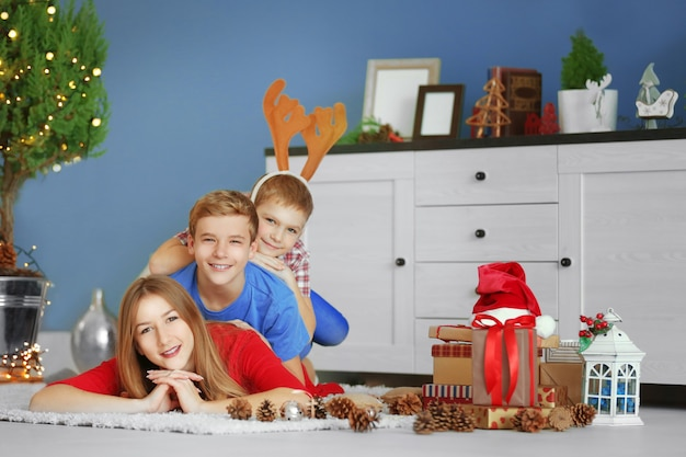 Happy sister and brothers with gifts on the floor in decorated christmas room