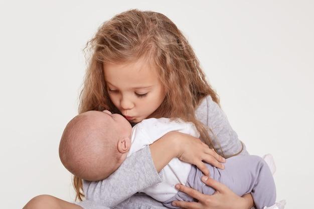 幸せな妹は、白に対して座って、女の赤ちゃんにキスします