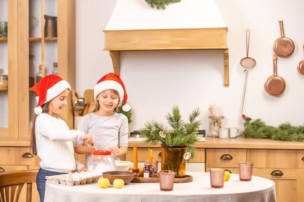 Счастливые сестры дети девочки печь печенье, месить тесто, играть с мукой и смеяться на кухне
