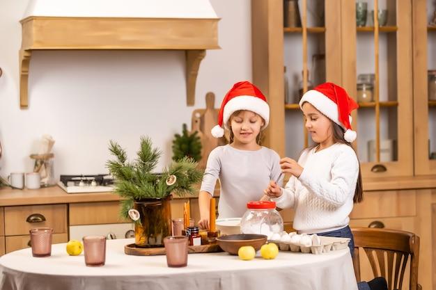 Счастливые сестры дети девочки две маленькие девочки готовят перед рождеством на кухне