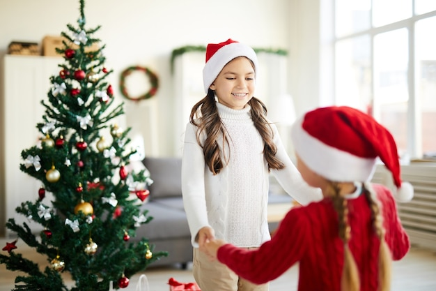 Happy sisters dancing and playing next to the christmas tree