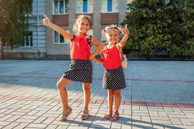 배낭을 메고 엄지손가락을 치켜드는 행복한 자매 소녀들. 야외 학교 건물에서 즐거운 시간을 보내는 아이들. 교육. 학교로 돌아가다