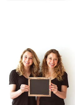 Happy sisters holding blank small slate in hands