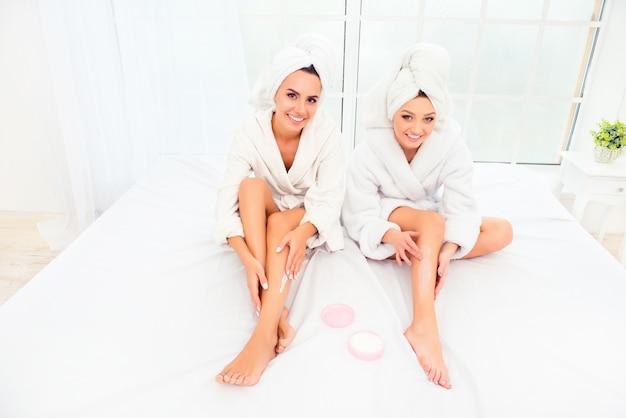 頭にバスローブとタオルを着て、脚にクリームを塗る幸せな姉妹