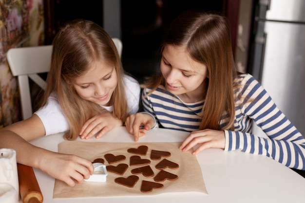 Счастливые сестры на домашней кухне за столом вырезали из теста печенье в форме сердца