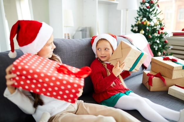Счастливые сестры сидят на диване и разворачивают рождественские подарки