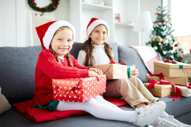 Happy sisters sitting on the sofa and unwrapping christmas presents