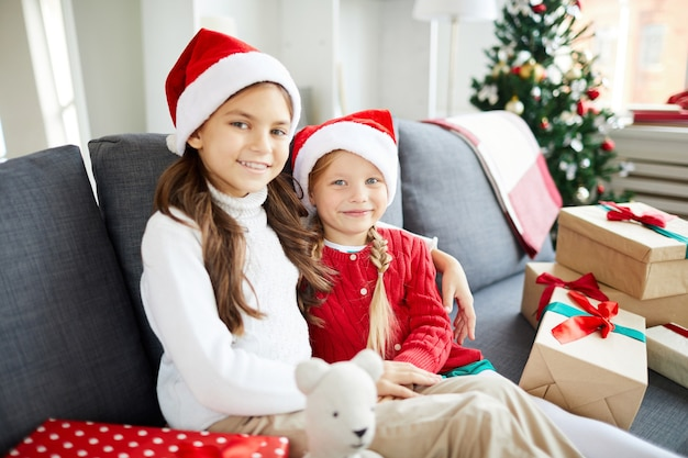 Happy sisters sitting on the sofa with christmas presents