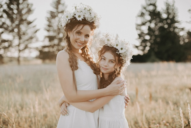 Happy sisters in white dresses with floral wreaths and boho style braids in summer in a field