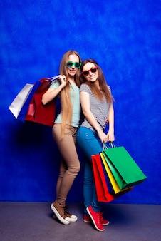 青いスペースで隔離の買い物袋と幸せな姉妹