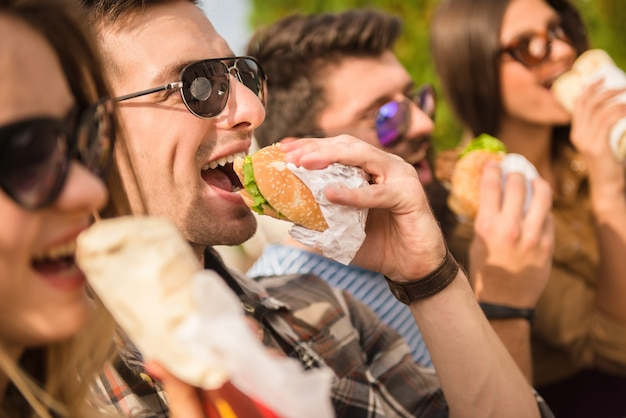 Happy sitting in the park and eat fast food with friends.