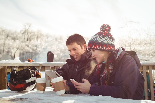 Happy skier couple sitting at the table while using mobile phone and digital tablet