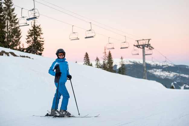 Happy skier female standing in the snowy mountains enjoying winter holidays against a ski-lift