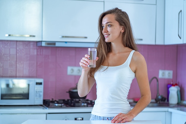 Happy sleepy joyful woman drinks a glass of clean purified morning water in early morning after waking up in the kitchen at home. beginning and start of a new good day