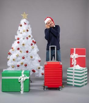 カラフルなクリスマスのおもちゃと白いクリスマスツリーの近くにサンタの帽子をかぶった幸せな眠そうな男