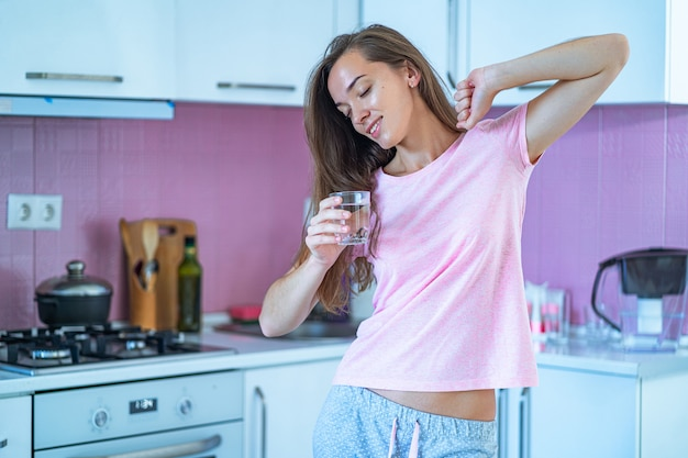 Happy sleepy woman in pajamas stretching and drinks a glass of clear purified water in morning after waking up in the kitchen at home. beginning and start of a new good day