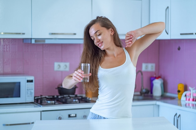 Happy sleepy woman stretching and drinks a glass of clean purified morning water in early morning after waking up in the kitchen at home. beginning and start of a new good day