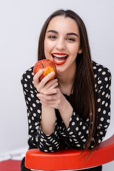 Happy slender woman holding apple isolated on a white background. looking at camera
