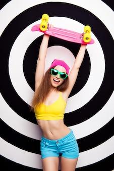 上げられたスケートを保持している眼鏡の幸せなスリムフィットの女の子