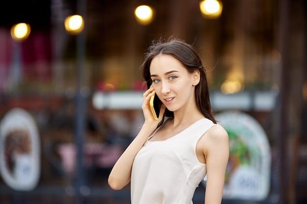 야외에서 스마트폰으로 행복한 슬림 여성 회담