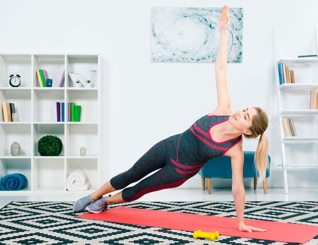 Happy slim young woman exercising in the living room