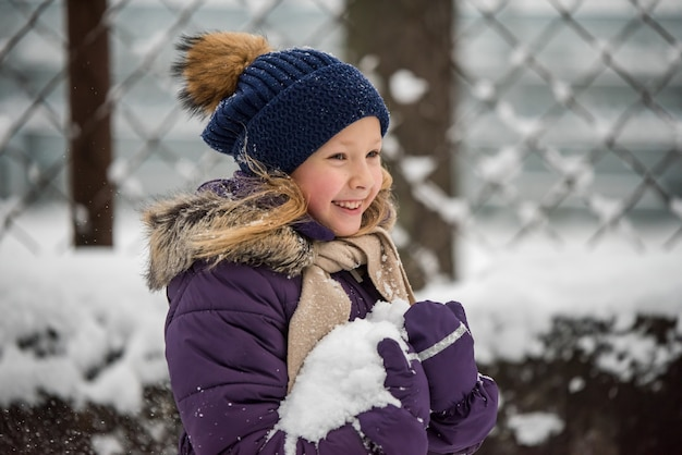 Happy small blonde girl child having fun playing with snow in winter day