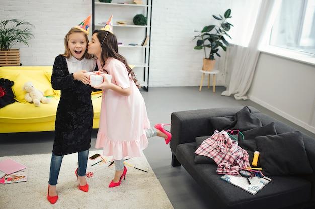 행복 한 작은 금발 소녀는 그녀의 친구로부터 선물을 잡아. 갈색 머리 그녀를 뺨에 키스. 십대는 성인 여성을위한 옷과 신발을 착용합니다. 그들은 방에서 행복해 보인다.