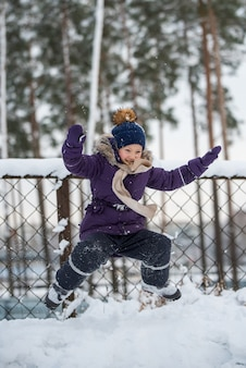 Happy small blonde girl jumping in the snow, child having fun playing with snow in winter day