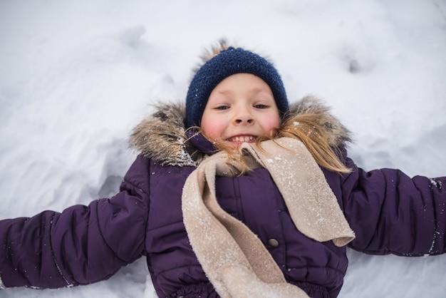 Счастливая маленькая блондинка лежит в снегу и делает ангела, ребенок веселится, играя со снегом в зимний день