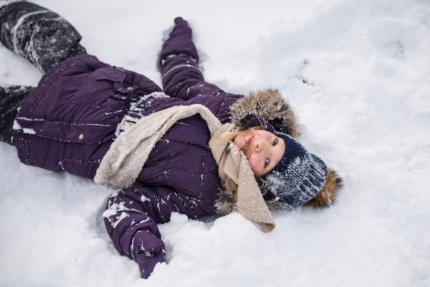 Happy small blonde girl lies in the snow, child having fun playing with snow in winter day