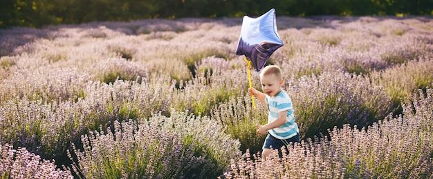 星の風船でラベンダー畑を走る幸せな小さな男の子