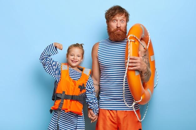 오렌지 구명 조끼에 행복 한 작은 아이가 팔을 들고 아버지와 손을 잡고 근육을 보여줍니다
