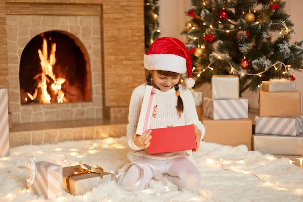 Happy small girl opening christmas present box, looks inside with smile, being happy to get such gift, wearing white pullover and santa claus hat, sitting on floor in festive room with xmas decoration