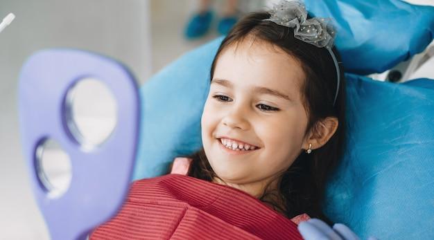 Счастливая маленькая девочка улыбается в зеркало после операции у стоматолога