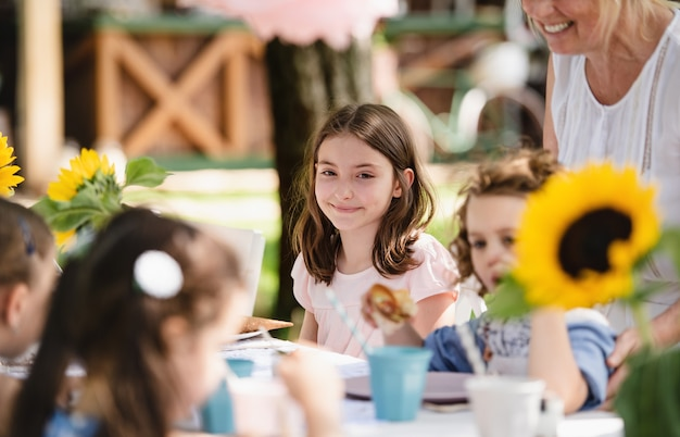 Happy small girls sitting and eating at table on summer garden party, birthday celebration concept.
