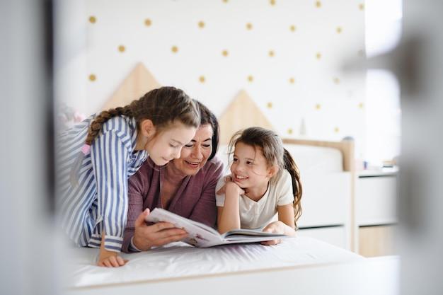 Счастливые маленькие девочки со старшей бабушкой в помещении в спальне дома, читая на кровати