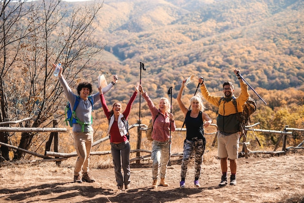 Happy small group of hikers standing on the glade with hands in the air in the autumn. in background mountains and forest.