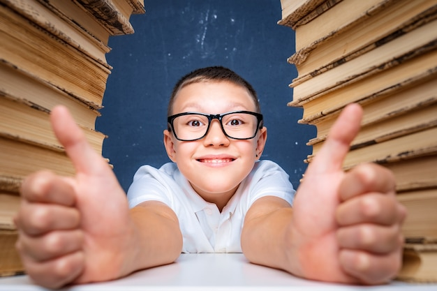 Happy smart boy in glasses sitting between two piles of books smiling and showing thumbs up.