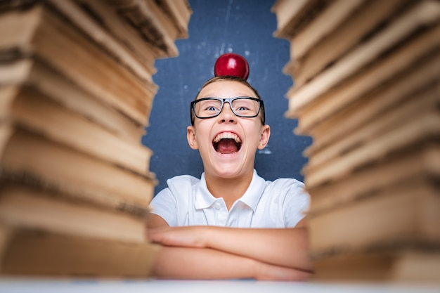 Happy smart boy in glasses sitting between two piles of books with red apple on head and look at camera smiling with open mouth.